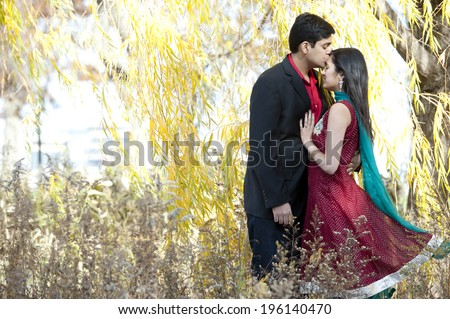 A young Indian man kissing the forehead of his Indian bride who is wearing a Sari and both are standing under a willow tree. - stock photo
