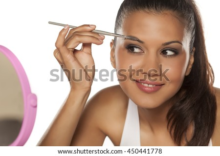 A young Indian woman shaping her eyebrows with a brush - stock photo