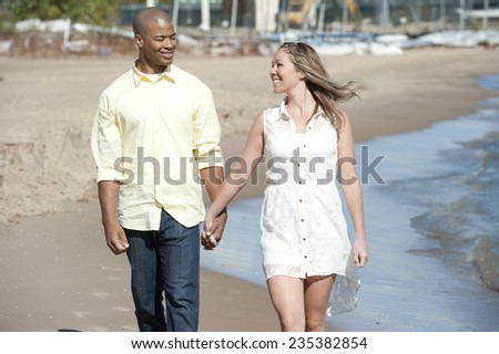 A young interracial couple walking on the beach on a sunny day. - stock photo