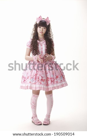 A young Japanese woman dressed in a pink dress of the Lolita style, a sub-genre of the kawaii phenomenon - stock photo