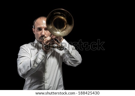 a young jazzer with a trombone over black background