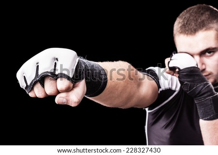 a young kickboxer or boxer isolated over a black background - stock photo