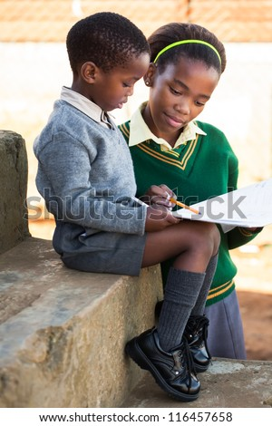 A young lady is helping her little brother with work.