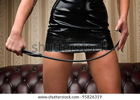 A young lady mistress with a whip, leather couch on background.