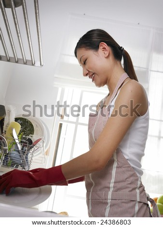 A young lady scrubbing the plate