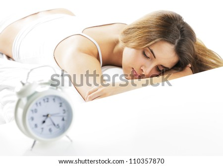 A young lady sleeping on the background with a clock on the foreground. - stock photo