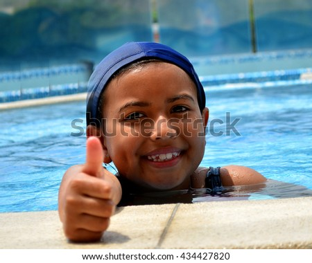 A young latinamerican girl in the swimming pool. - stock photo