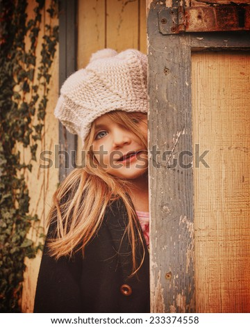 A young little child is wearing a white winter hat and looking out against an old shed door for a season or memory concept. - stock photo