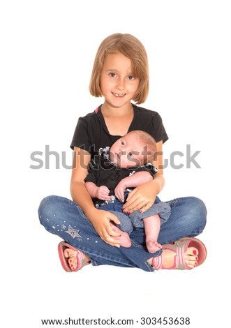 A young little girl holding her three weeks old brother in her lap and