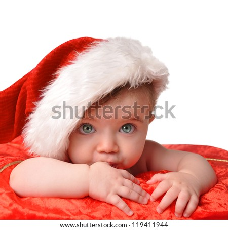 A young little santa baby is wearing a christmas hat on a red blanket with an isolated background. - stock photo
