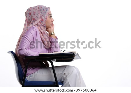 A young malay muslim lady student is paying attention in class isolated on white background - stock photo