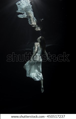 A young male ballet dancer is dancing underwater