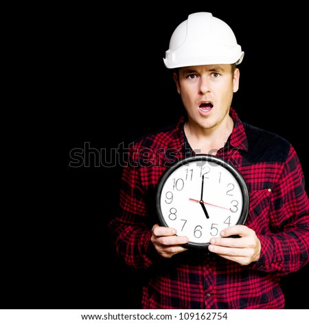 A young male builder holding clock with a look of stress and dismay in a depiction of a construction project running over schedule