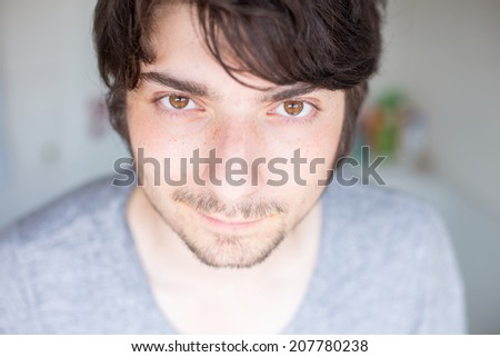 A young male, dark haired student is looking attractively at the camera - stock photo
