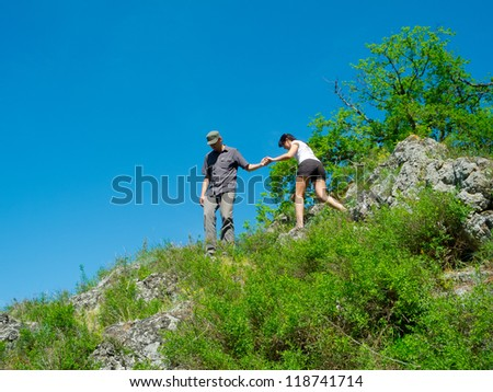A young male hiker is helping a female hiker to climb a mountain - stock photo
