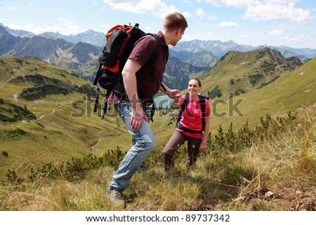 A young male hiker is helping a female hiker to climb a mountain in the Alps. - stock photo