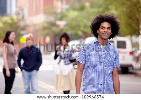 A young male in a city setting with friends in the background - stock photo