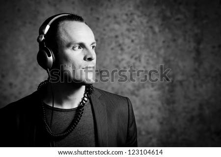 A young male listening to his music while posing in front of a grungy background. - stock photo