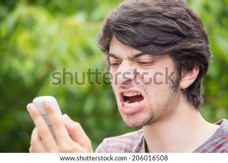 A young male model is angry at his phone - stock photo