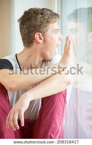 A young male model is pressing his nose against his own reflection in a window and touching it with his hands. He is angry!