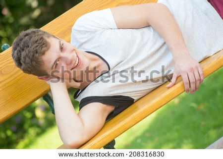 A young male model is smiling at the camera and laying relaxedly on a beautiful wooden bench in a green garden resting his head on his arm - diagonal - stock photo