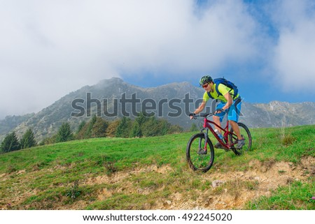 A young male riding a mountain bike outdoor in the mountain