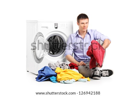 A young male sitting next to a washing machine isolated against white background