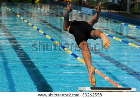 A young male swimmer jumps off the blocks at the start of a race.