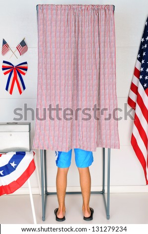 A young male voter inside a Voting Booth at his local polling place. Vertical format - man is unrecognizable. - stock photo