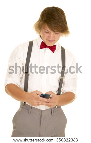 a young man all dressed up using his phone to text.