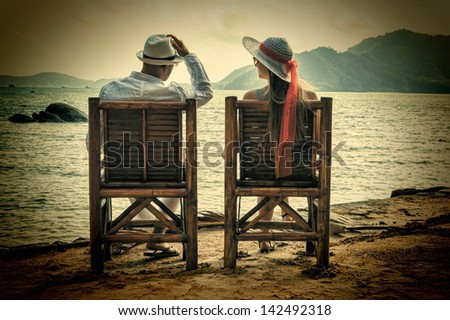 a young man and a girl sitting on the beach - stock photo