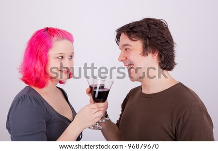 A young man and a young woman are drinking a glass of wine