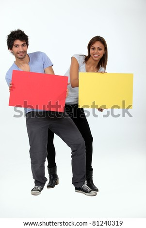a young man and a young woman calling attention by showing panels - stock photo