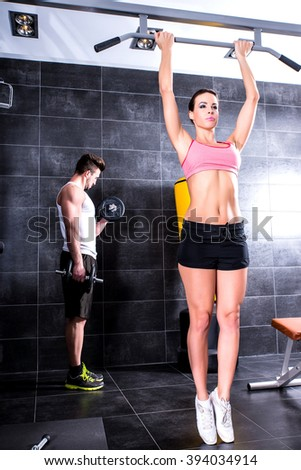A young man and a young woman working out in the Gym.