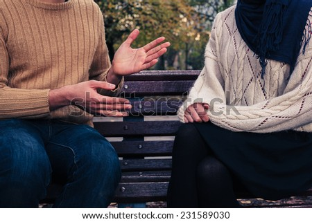 A young man and woman are sitting on a park bench and arguing - stock photo