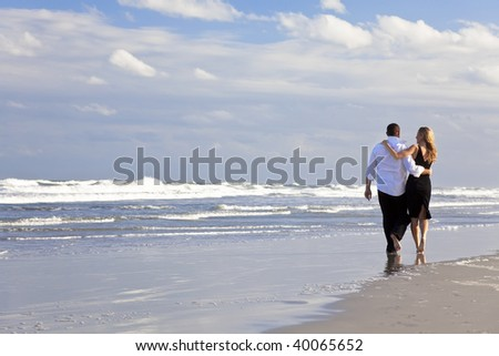 A young man and woman arms around each other walking as a romantic couple on a beach