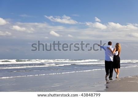 A young man and woman couple having a romantic walk on a beach with a bright blue sky