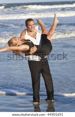 A young man and woman couple having romantic fun in the sea on a warm sunny beach