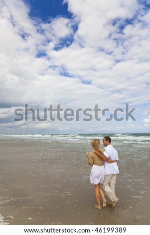 A young man and woman couple having romantic walk on a beach