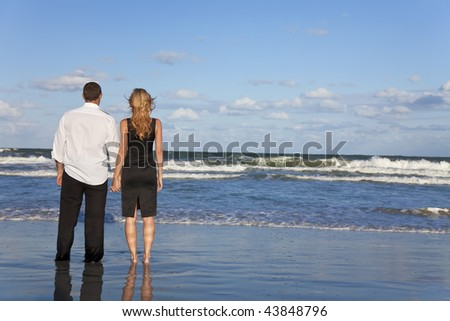 A young man and woman holding hands as a romantic couple looking out to sea on a beach with a bright blue sky