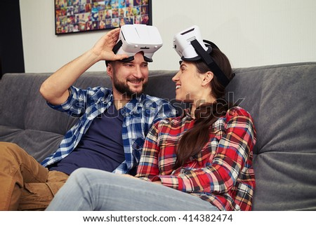 A young man and woman in casual clothes and virtual reality glasses is resting after playing virtual reality computer games - stock photo