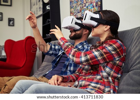 A young man and woman in casual clothes and virtual reality glasses is watching something and trying to touch something in front of them