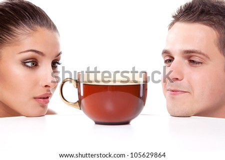 A young man and woman looking at a large cup of tea placed on a table in front of their noses - stock photo