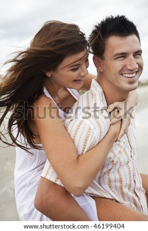 A young man and woman romantic couple having fun playing piggy back on a beach and laughing together.