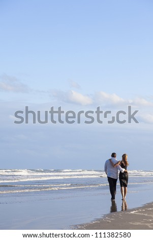 A young man and woman romantic couple walking embracing on a beach with a bright blue sky - stock photo