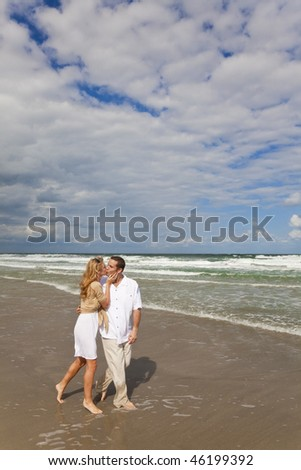 A young man and woman walking and kissing as a romantic couple on a beach - stock photo