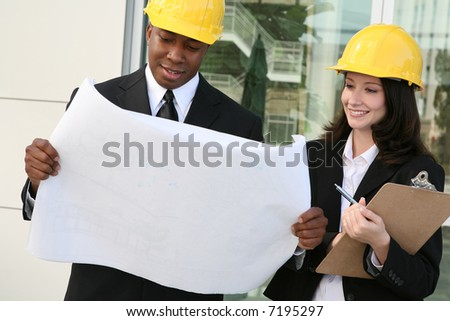 A young man and woman working as  architects on a building site