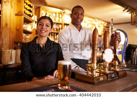 A young man and woman working behind a bar look to camera - stock photo