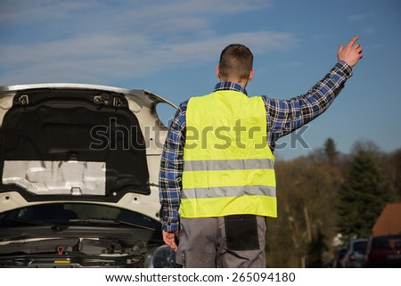 A young man asks for help on the road near her broken car - stock photo