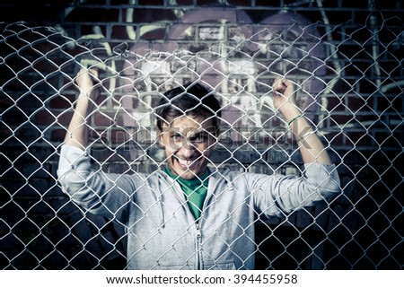 a young man behind bars close - stock photo